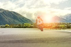 Man riding motorcycle on highway against mountain scene Stock Images