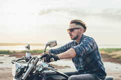 Man riding motorcycle. Hipster male on motorcycle in countryside stock photo