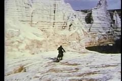 Man riding motorcycle through mountain terrain stock footage