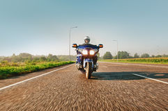 Man riding a motorcycle on an open road Stock Photos