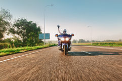 Man riding a motorcycle on an open road Royalty Free Stock Image