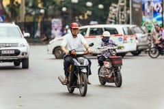 Man riding motorcycle on the road in Hanoi, Vietnam.  Stock Photos