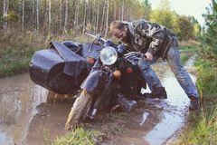 A man riding a motorcycle with a sidecar got stuck on the road in forest Royalty Free Stock Photo