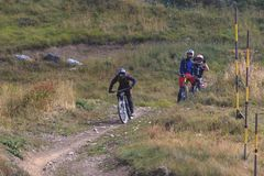 Man riding mountain bicycle downhill and two friends watching him royalty free stock images