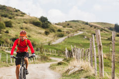 Man riding mountain bike on country road Royalty Free Stock Images