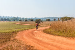 Man riding a mountain bike on a dirt road Stock Images