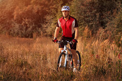 Man is riding a mountain bike in the field Stock Photo