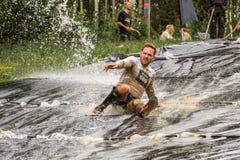 Man riding a muddy water slide. royalty free stock photo