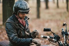 Motorcyclist sits on an old cafe-racer motorcycle, autumn background. Man Riding old custom cafe-racer Motorcycle on Country Road Stock Photos