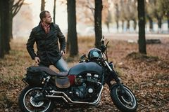 Motorcyclist sits on an old cafe-racer motorcycle, autumn background Royalty Free Stock Images