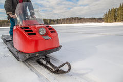 A man riding old red snowmobile on snow-covered lake. Around a spruce forest Royalty Free Stock Image