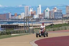 Man Riding Peddle Car on Beachfront Promenade stock photo