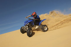 Man Riding Quad Bike In Desert. Low angle view of a man riding quad bike in desert against the blue sky Royalty Free Stock Photos