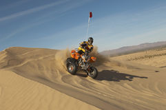 Man Riding Quad Bike In Desert. Low angle view of a man riding quad bike in desert on a sunny day Royalty Free Stock Photo