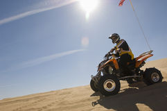 Man Riding Quad Bike In Desert Stock Photo