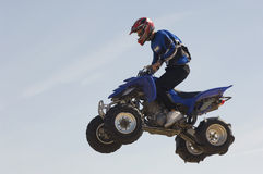 Man Riding Quad Bike In Midair Against Sky. Low angle view of a man riding quad bike in midair against the blue sky royalty free stock images