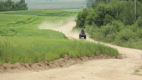 Man riding a quad bike on the sandy road along the field, smoke, dust stock video
