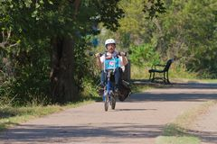 Man riding a recumbent bike with panniers and a white helmet. Man riding a recumbent bike royalty free stock photos