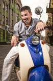 Man riding retro scooter Stock Image