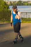 A man riding on roller skates talking on a mobile phone Royalty Free Stock Image