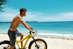 Man Riding Sand Bicycle On Beach. Summer Sport Activity. Summer Beach Sport. Athletic Man With Muscular Body Riding Yellow Sand Bicycle At Tropical Seaside stock image