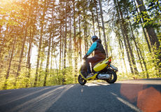 Man riding scooter on forest road. Stock Image
