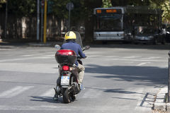 Man riding scooter. A man with a helmet is riding a scooter in the photo he is stopped at the traffic lights. In the background a public bus dedicated to the Royalty Free Stock Image