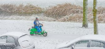 Man riding a scooter in the snow royalty free stock images