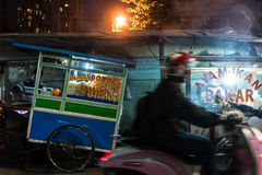 Man riding a scooter on a street with food stalls in a poor dist. Side view of a man riding a scooter on a street with traditional food stalls in a poor district stock photos