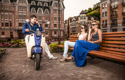 Man riding on scooter and talking to beautiful girls Royalty Free Stock Image