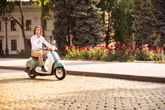Man riding a scooter through town streets Royalty Free Stock Photography