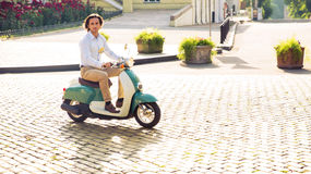 Man riding a scooter in town Stock Photos