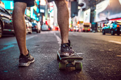 Man riding on skateboard in New York City street at the night. Male legs with skateboard in night city Stock Image