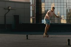 Man riding on skateboard on rooftop Royalty Free Stock Image