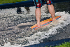 Man riding a small surfboard along a water slide Stock Images