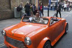 The man is riding in a small vintage red car. The crowd looks at him. Bricklane Royalty Free Stock Photography