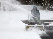Man on Riding Snowblower with Blowing Snow. Front view of upper middle-aged caucasian man riding on tractor-style snowblower clearing a residential driveway Stock Image