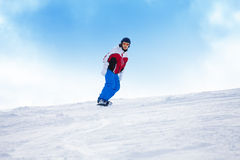 Man riding on the snowboard down mountain hill Royalty Free Stock Photos