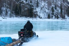 Man riding on a snowmobile  frozen water Royalty Free Stock Photography
