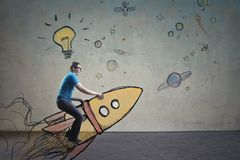 Man riding a space rocket. With a drawing on the background Stock Images