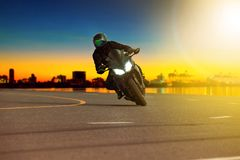 Man riding sport motorcycle leaning in sharp curve with traveling scene background stock photography