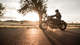 Man riding sportster motorcycle during sunset. Royalty Free Stock Image