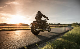 Man riding sportster motorcycle during sunset. Royalty Free Stock Images
