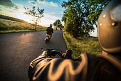 Man riding sportster motorcycle during sunset. Stock Photos