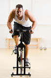Man Riding Stationary Bicycle In Health Club Royalty Free Stock Photos