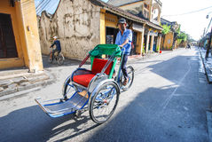 Man riding a traditional cyclo in Hoi An Stock Images
