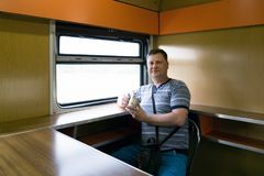 A man is riding in a train restaurant. royalty free stock photos