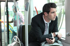 Man riding tram to work Stock Images