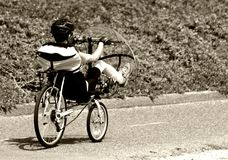 Man riding a unique bike with a windshield Stock Images