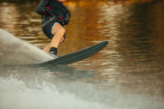 Man riding wakeboard on a lake. Male water skiing and surfing across the lake Royalty Free Stock Photos